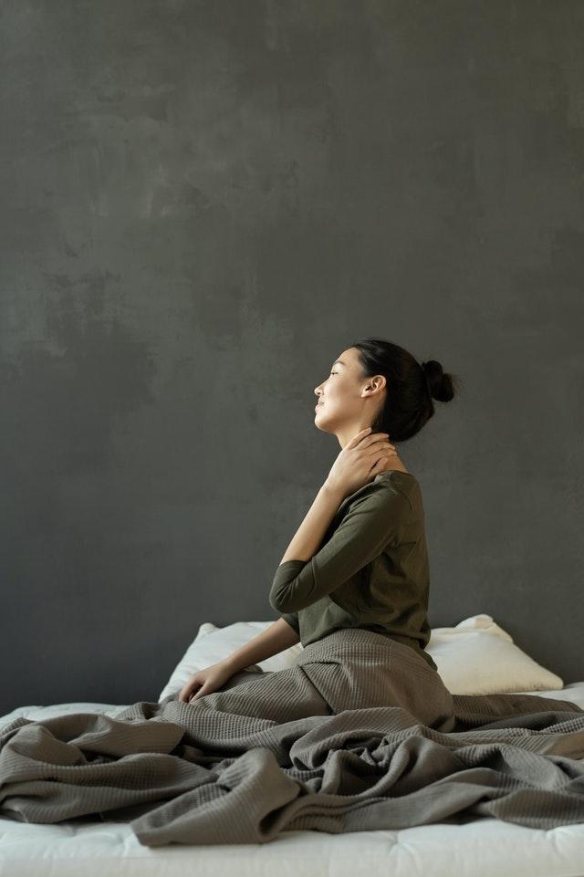 women sitting on bed needing neck pain treatment